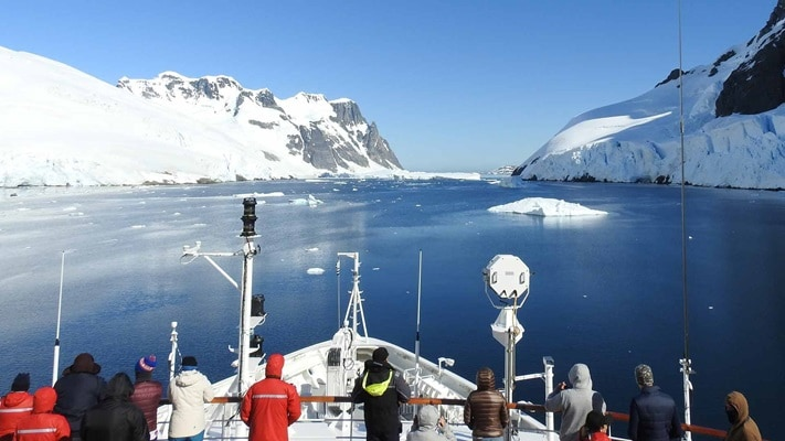 Row of passengers at front of ship watching clear icy water and mountains, Antarctica