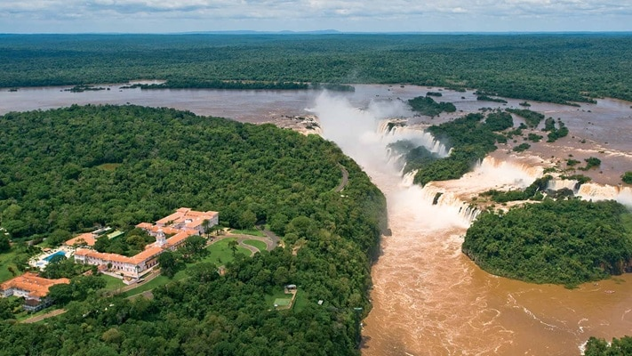 Hotel overlooking water falls with brown water below, South America