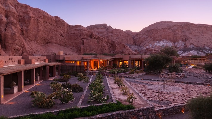 Hotel in the desert with rocky cliff behind it