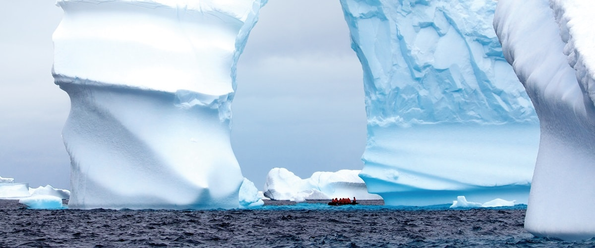 Zodiac cruising under a huge iceberg arch