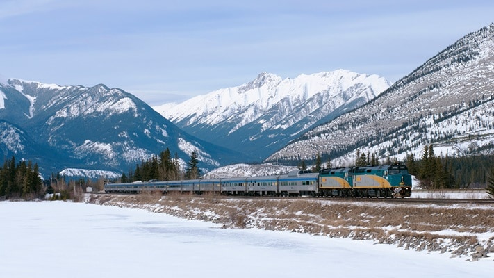 Train travelling past the snow capped mountains in winter